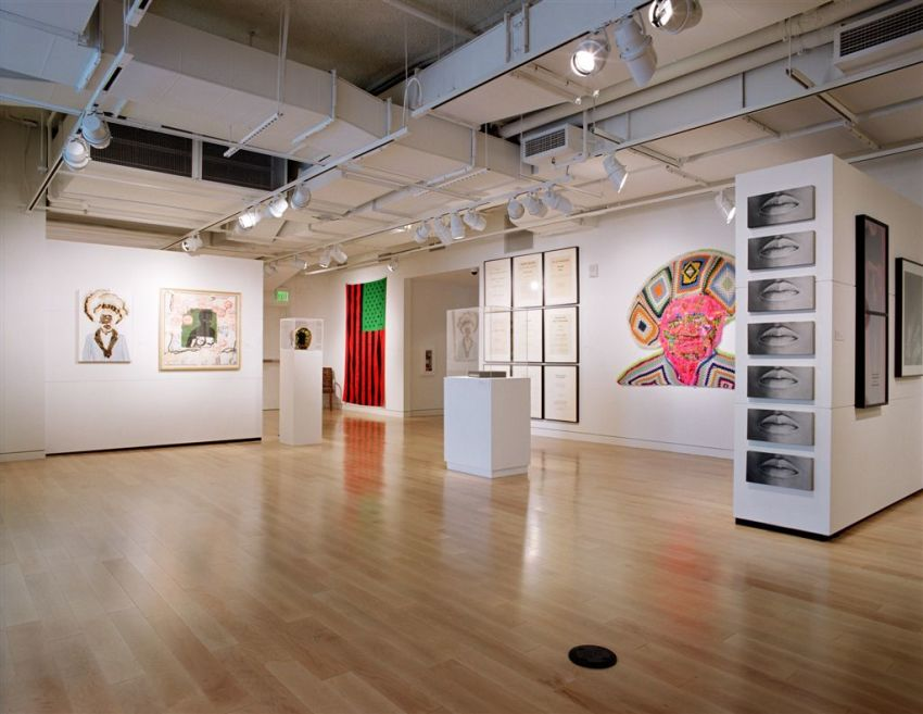 A glimpse of the exhibition space: an industrial ceiling, spotlights that shine down on hardwood floors, the reflection of the perforated walls of the museum and exhibition islands, all create a gallery for viewing.