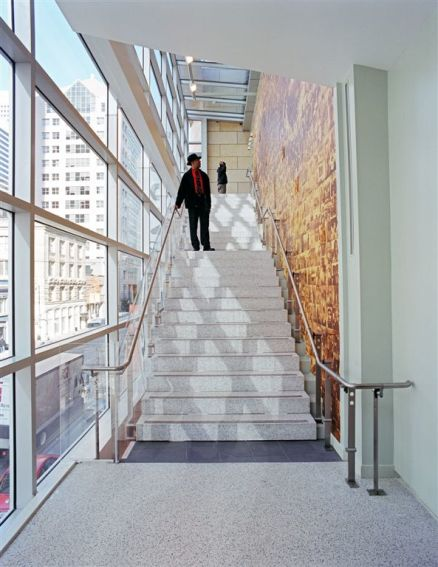 On the outskirts: On the left, large windows capture the vibrant urban quality of the surrounding context and on the right the museum captivates the visitor.  On the stairs a cascading shadow from the window frames creates a diamond pattern of sunlight spanning each step.